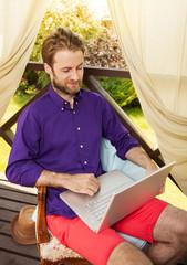 Man looking at laptop computer outdoor on garden terrace