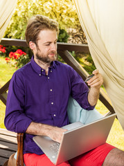 Man looking at credit card while working on laptop computer