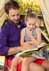 Father and daughter reading book on garden terrace
