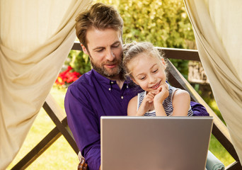 Father and daughter looking at laptop computer in the garden