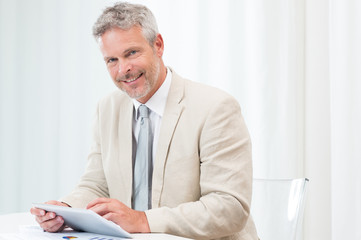 Happy Mature Businessman With Tablet