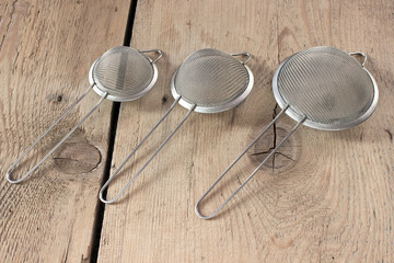 Three colanders on wooden background