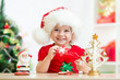 child girl in Santa hat holding Christmas cookies