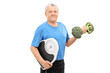 Senior holding broccoli dumbbell and weight scale
