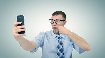 Funny bearded businessman photographing himself on a smartphone