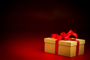 Golden Present Box With a Red Ribbon