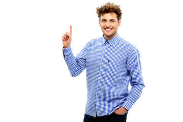 Happy casual man pointing upwards over white background