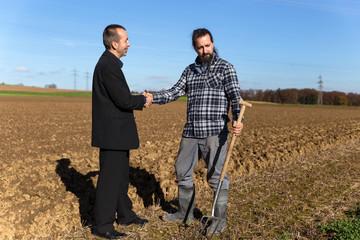 Geschäftsmann handelt mit Landwirt Vertrag aus