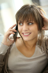 Portrait of young woman at home talking on mobile phone