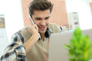 Student in front of laptop talking on mobile phone