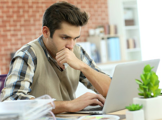 Young man working on laptop computer in office