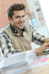 Young office worker using headphones in front of laptop