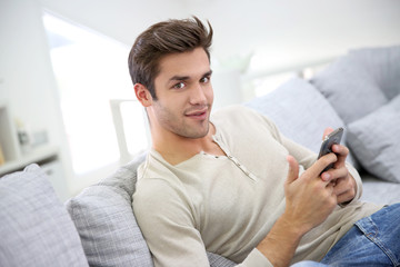 Smiling handsome man with smartphone relaxing at home