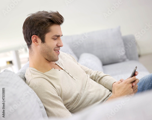 canvas print picture Smiling handsome man using smartphone sit in couch