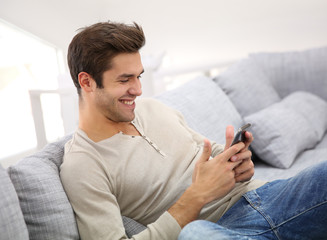 Man with smartphone being happy as reading message