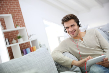 Young man with headphones watching movie on digital tablet
