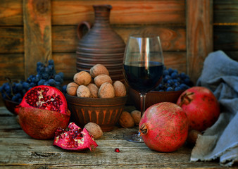 pomegranate, walnuts and glass of wine on a wooden background