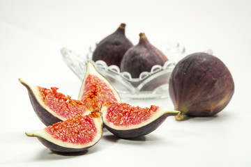 fresh figs with glass bowl, fork and knife isolated on white bac