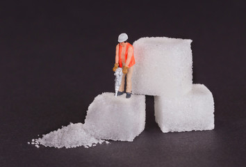 Miniature worker working on a sugar cube