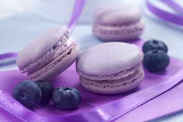 Violet French macaroons cookies and blackcurrant on horizontal