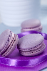 Three violet French macaroons cookies and ribbon