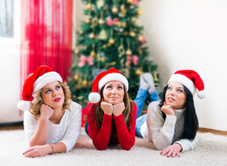 Three beautiful young women in front of a Christmas tree