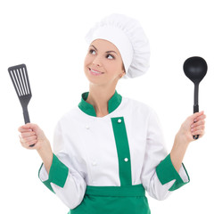 dreaming woman in green chef uniform with kitchen tools isolated