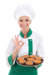 young chef woman in uniform holding tray with muffins and showin