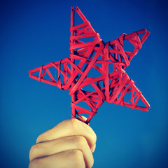 man holding a red christmas star