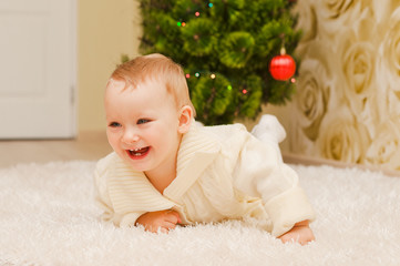 Girl sitting on a light carpet, smiling, looking at the camera.