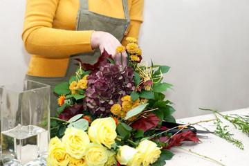 Florist making a bouquet of different cut flowers
