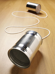 Two tin cans joined with a cord on a wooden