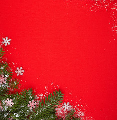 Gifts and Christmas tree branch in the snow and red background,