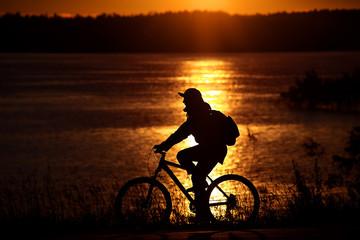 Велосипедист на берегу реки на закате Солнца