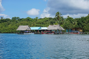 Tropical restaurant over the sea with boat at dock