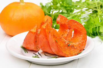 Slices of roasted pumpkin on white plate,