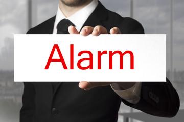 Geschäftsmann in Büro hält Schild Alarm