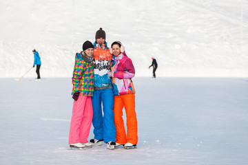 Young people, friends, winter ice-skating on the frozen lake