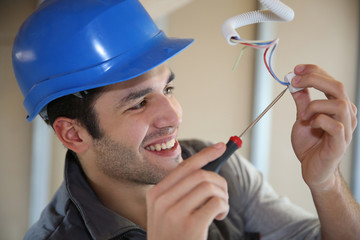 Young electrician working on building site