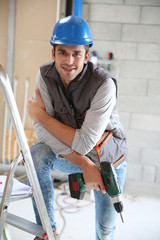 Construction worker holding electric drill