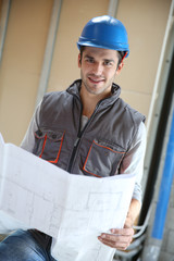 Contractor reading contruction blueprint on site