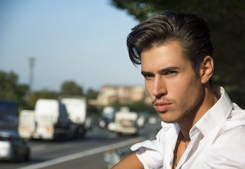 Handsome young man and busy road with traffic