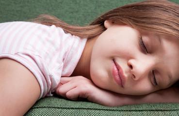 face of a little sweet girl sleeping on a sofa