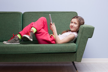 little girl enjoying a tablet on her sofa