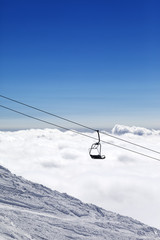 Ski slope, chair-lift and mountains under clouds