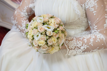 Beautiful wedding bouquet in hands of the bride with roses