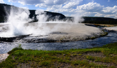 Erupting geyser on a riverbank in Yellowstone national park