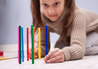 little girl playing with her coloured felt-tip pens