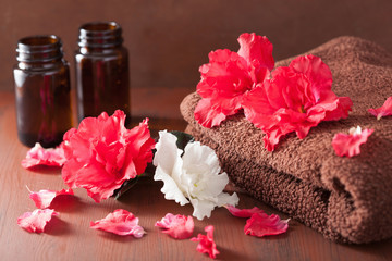 spa bathroom with azalea flowers essential oil on dark rustic ba
