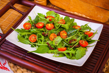 Vegetables on plate: arugula, spinach and tomatoes